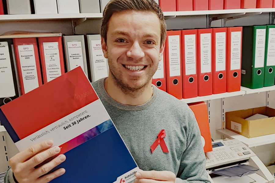 Deniz Kurku mit Broschüre der Aids-Hilfe